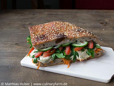 Sandwich mit frischem Fladenbrot, Hummus, Rucola, Tomaten, Gurke und Karotte