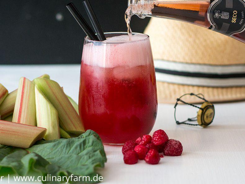Sommerlicher Drink mit Rosé-Champagner, Rhabarbersaft, Himbeeren und Wodka